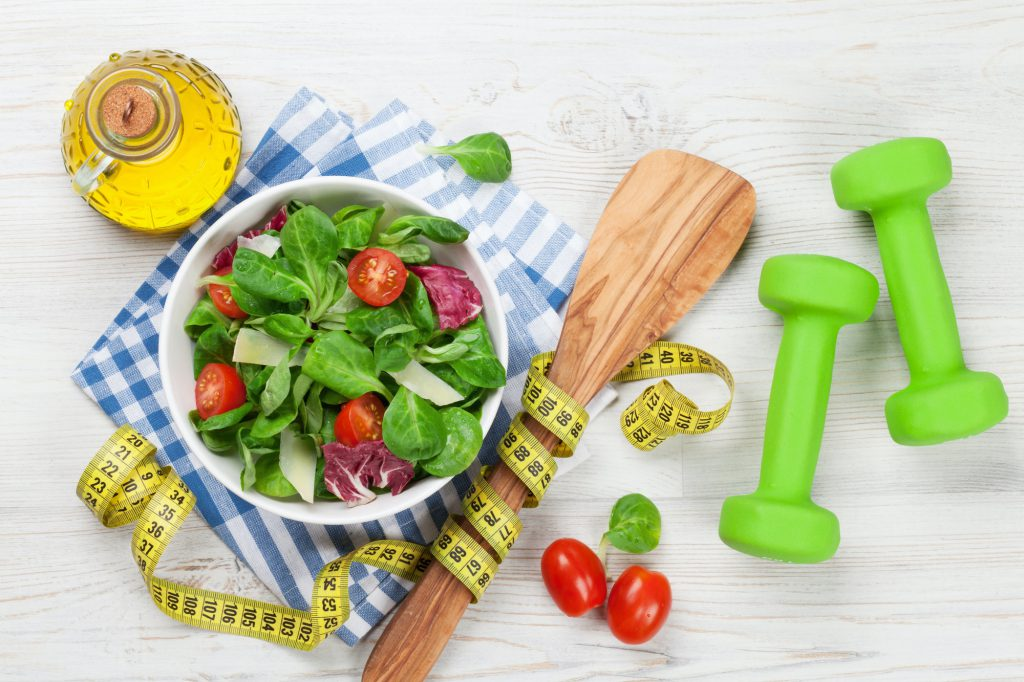 Healthy salad and fitness equipment