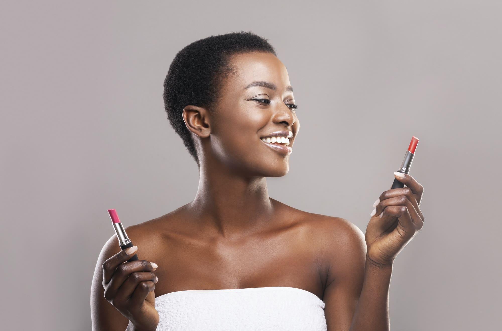 African american woman choosing between two lipstick colors