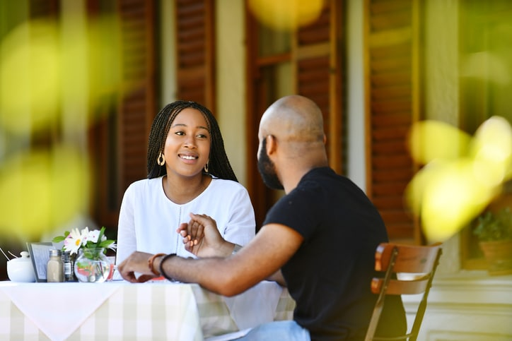 Young African couple sitting on a veranda holding hands