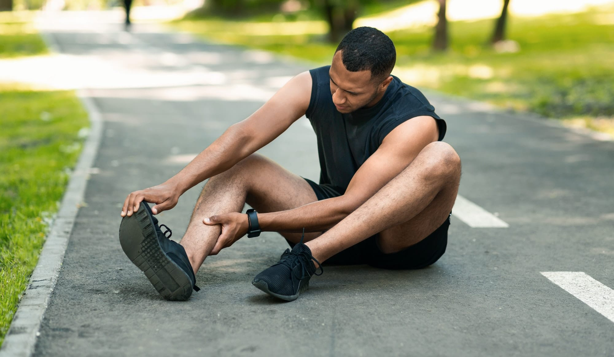Sports injury. African American runner sitting on jogging track and feeling pain in his ankle
