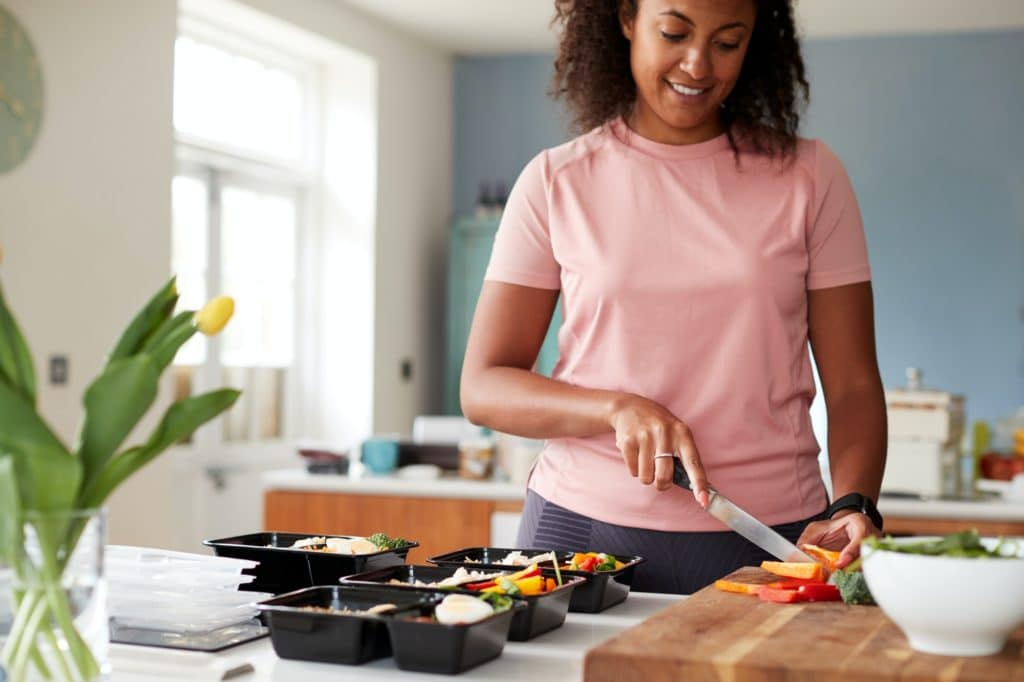 Woman Preparing Batch Of Healthy Meals At Home In Kitchen