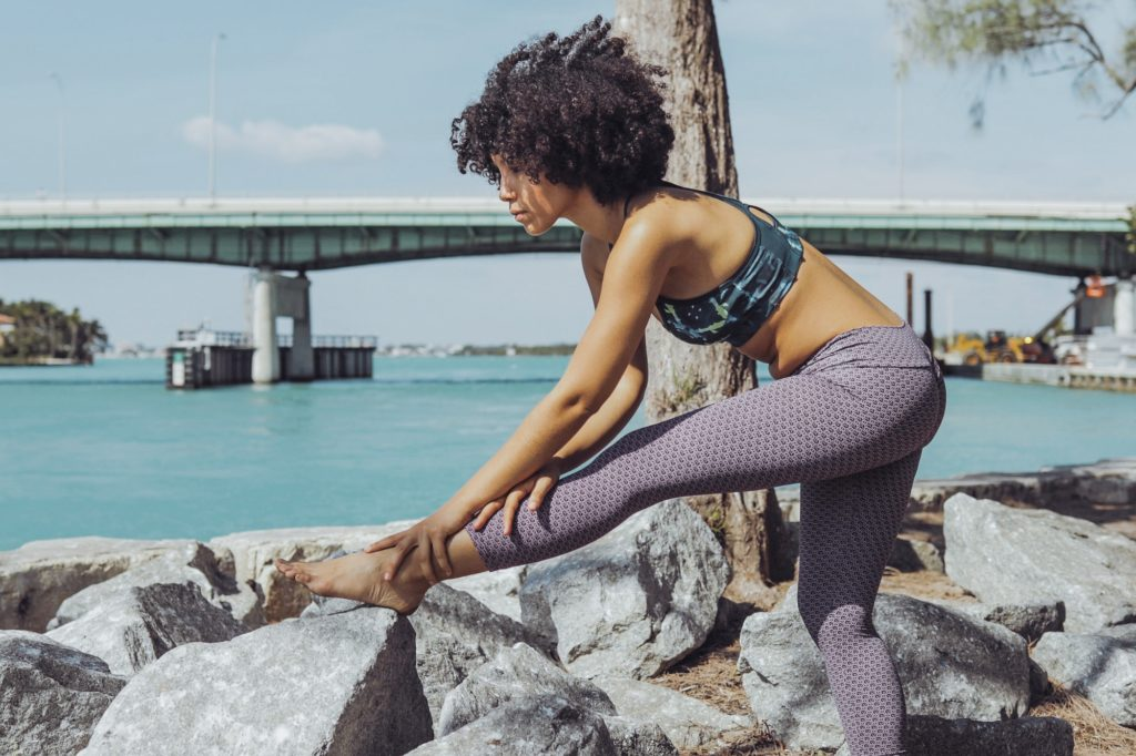 Black girl working out on riverbank