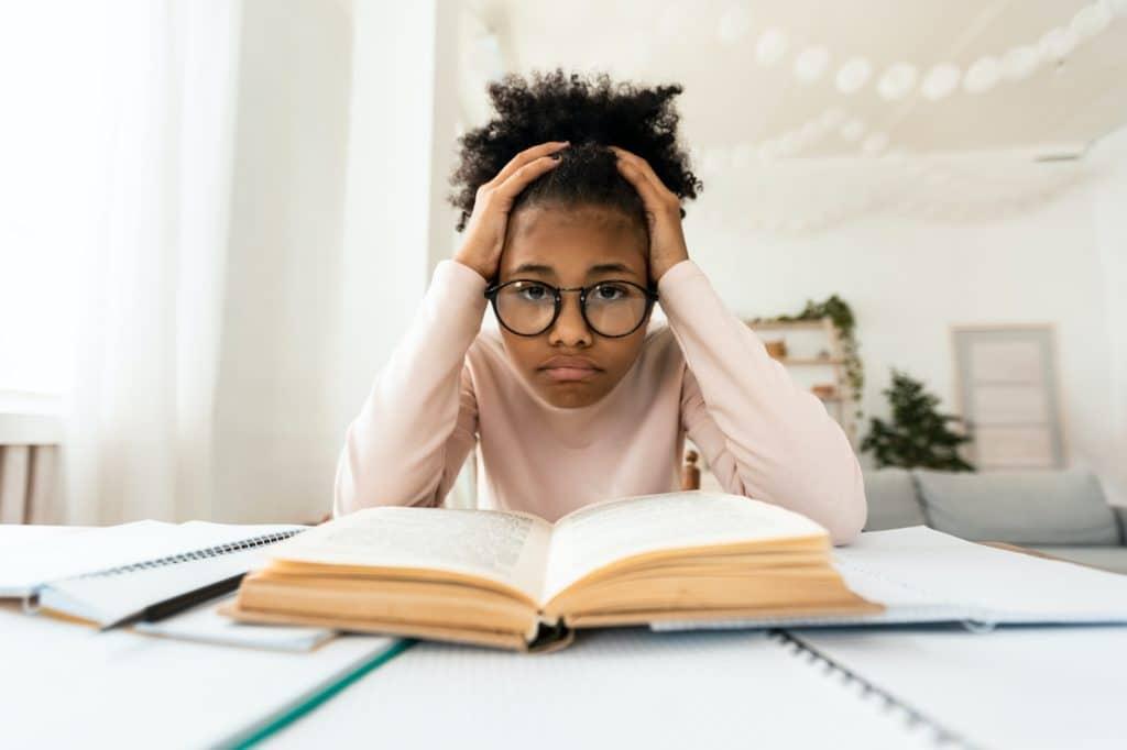 Frustrated Black Girl Looking At Camera Sitting At Book Indoors