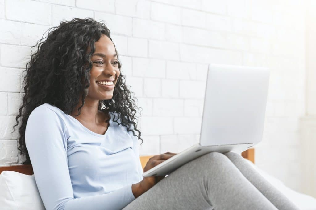 Happy young afro lady chatting online in bedroom