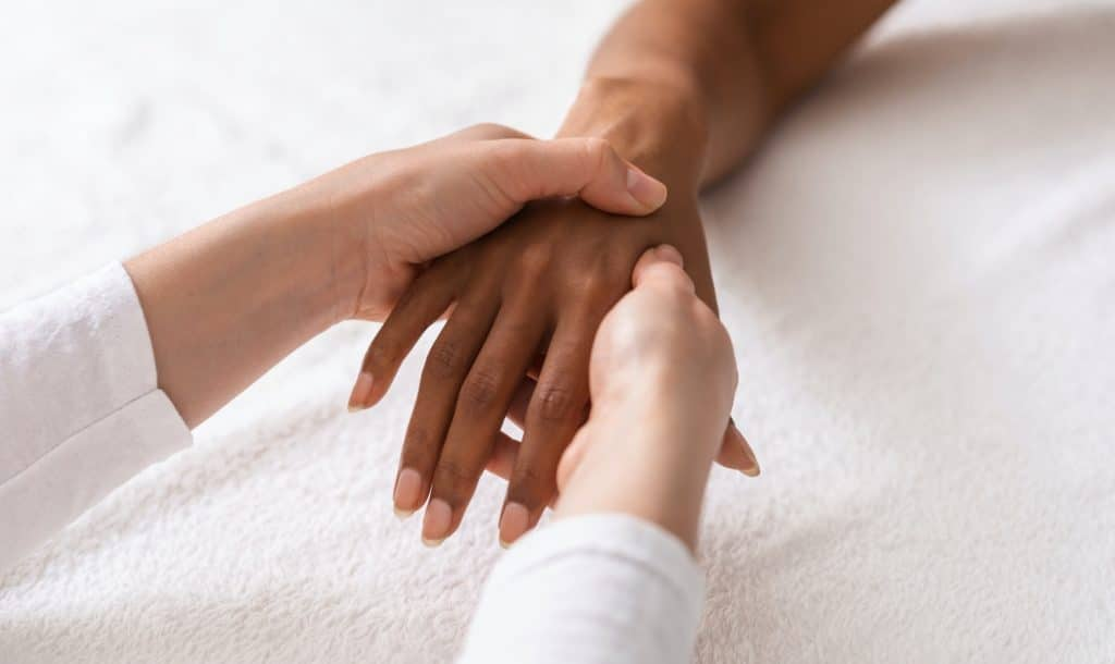 Masseuse making acupuncture hand massage for black woman