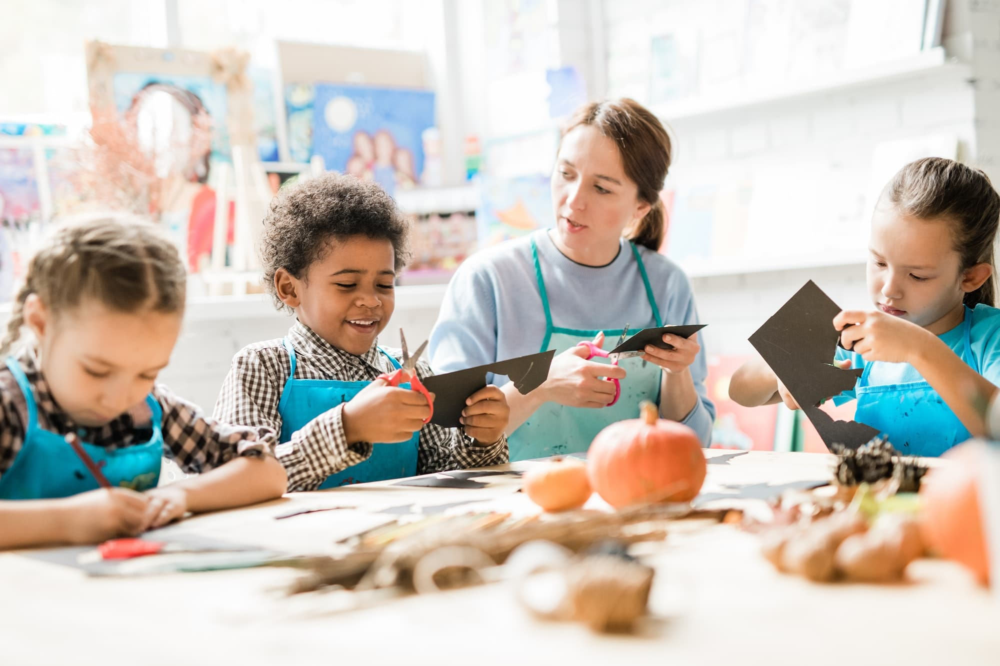 Multiracial schoolkids and teacher in aprons cutting out halloween decorations