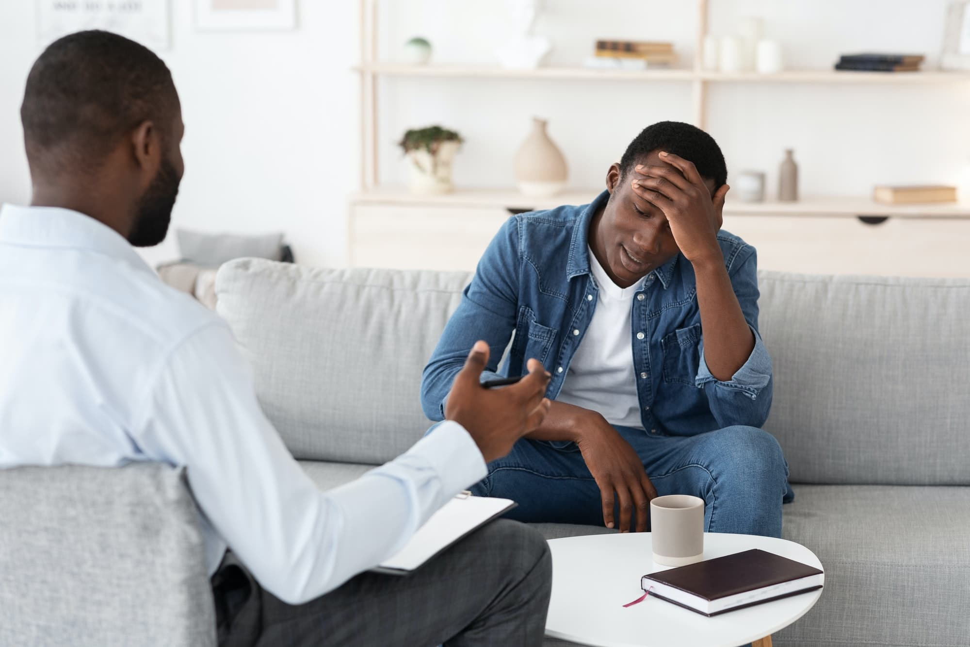 Psychotherapy Concept. Depressed black man talking to psychologist during individual therapy