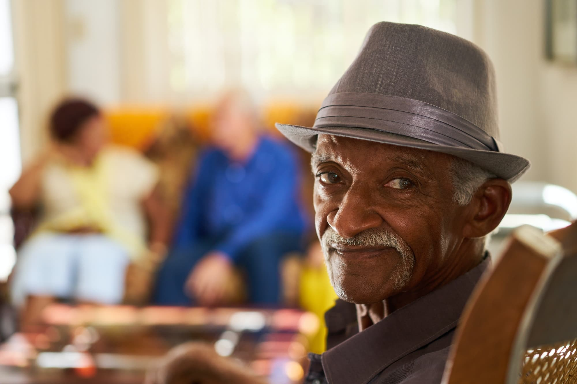 Senior Black Man With Hat Looking At Camera In Hospice