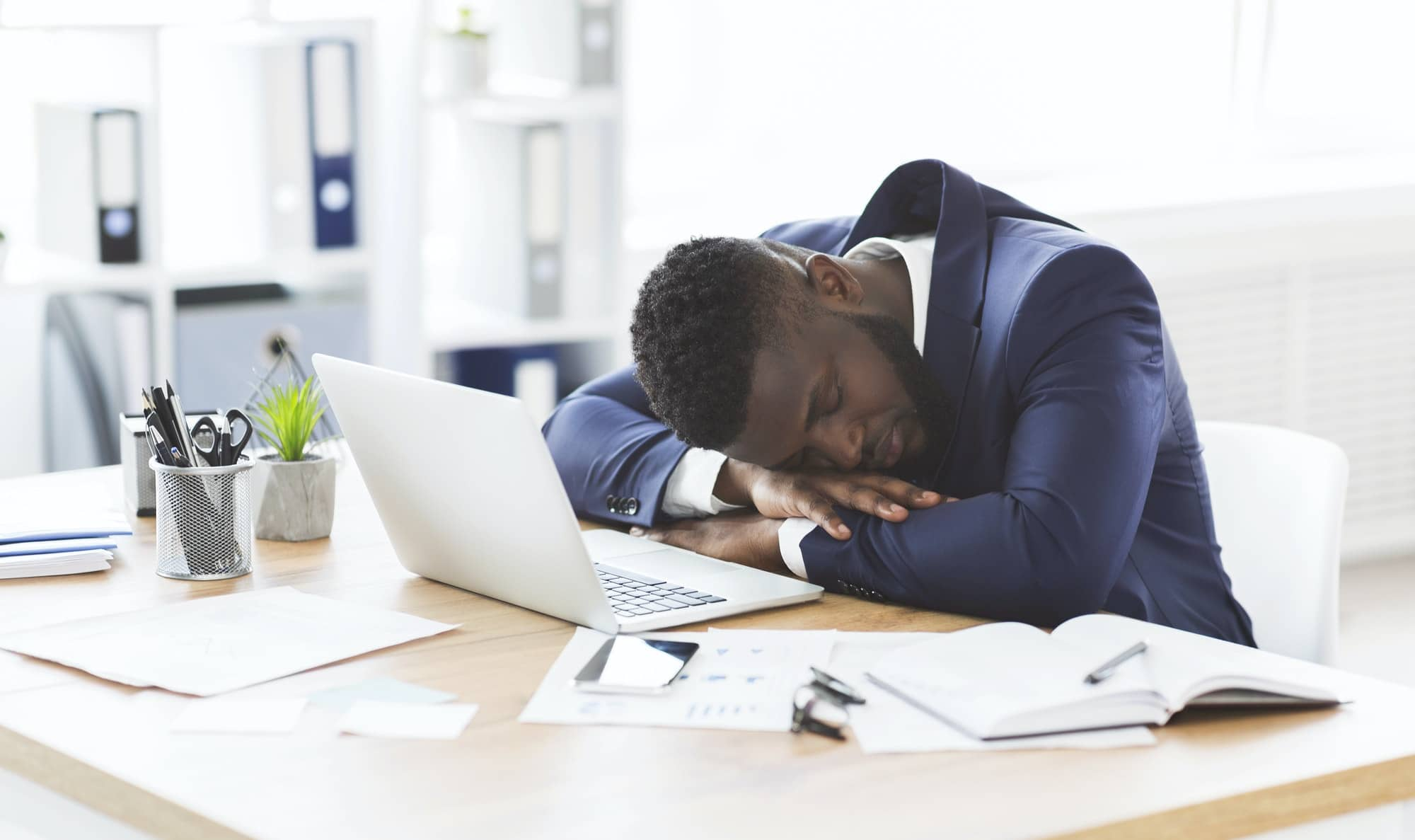 Tired black businessman sleeping in his office