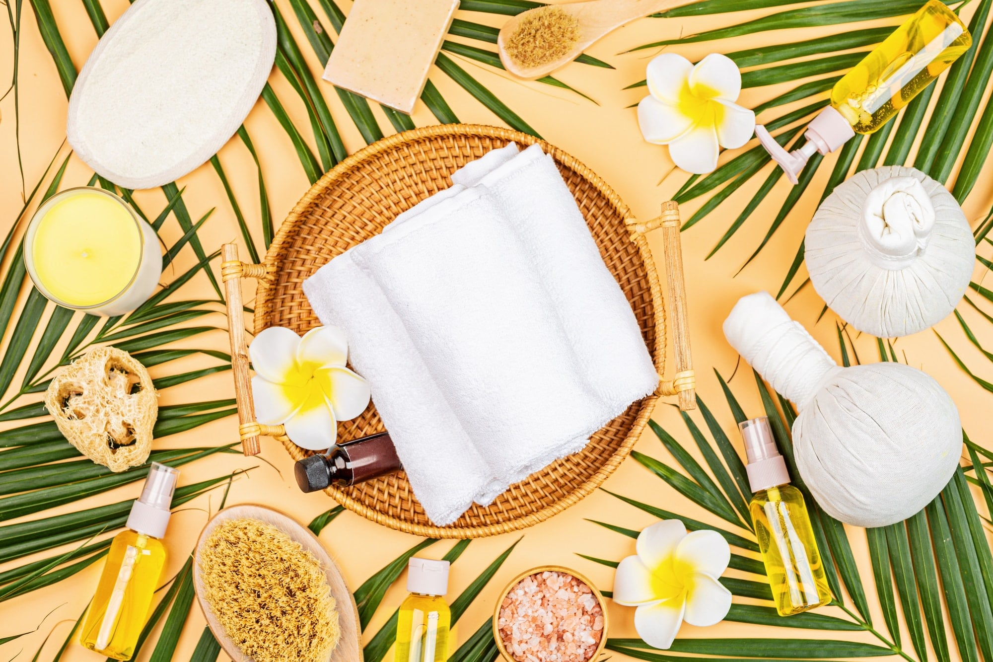 Spa massage Aromatherapy body care background. Spa herbal balls, cosmetics, towel and tropical leaf