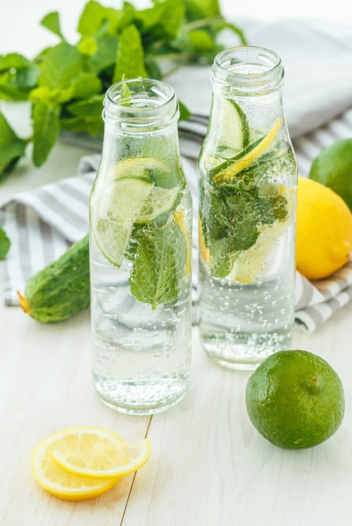 Infused water with citrus and mint in glass bottles