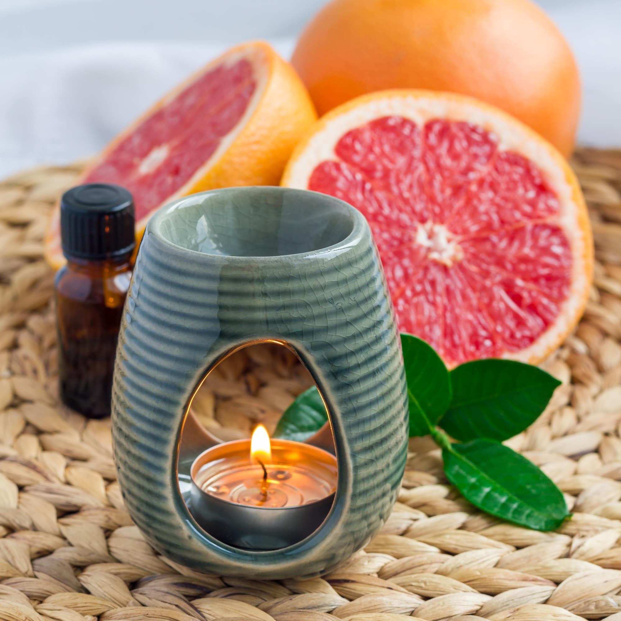 Aroma lamp with grapefruit essential oil on woven mat, grapefruits on background, square format