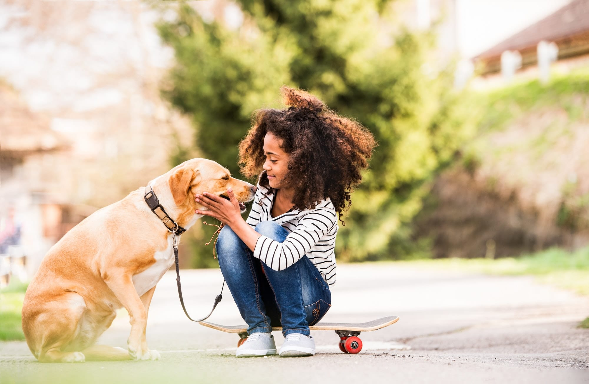 African american girl outdoors on skateboard with her dog.