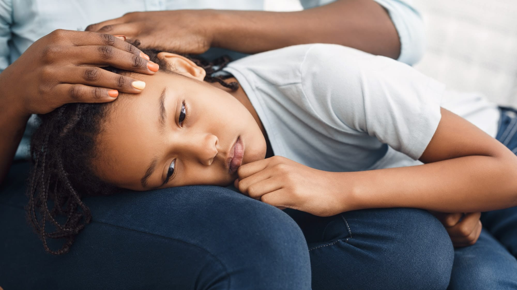 Close-up of black girl's head laying on lap