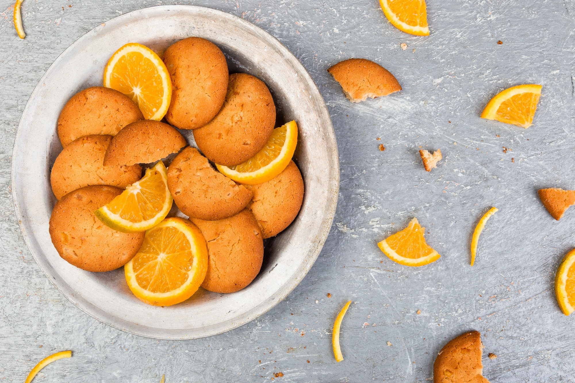Cookies and orange citrus fruit on metal plate on grey background. Flat lay