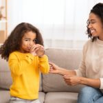 Mother Feeding Daughter, Caring For Kid Sitting On Couch Indoor