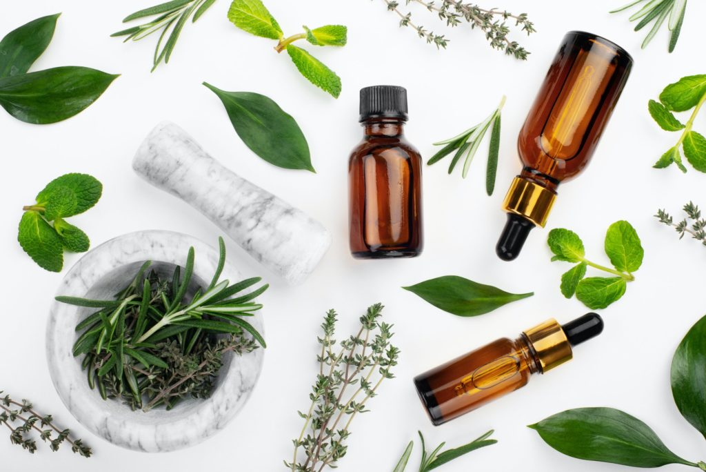Dropper bottles with oil and mortar with herbs on white table flat lay view