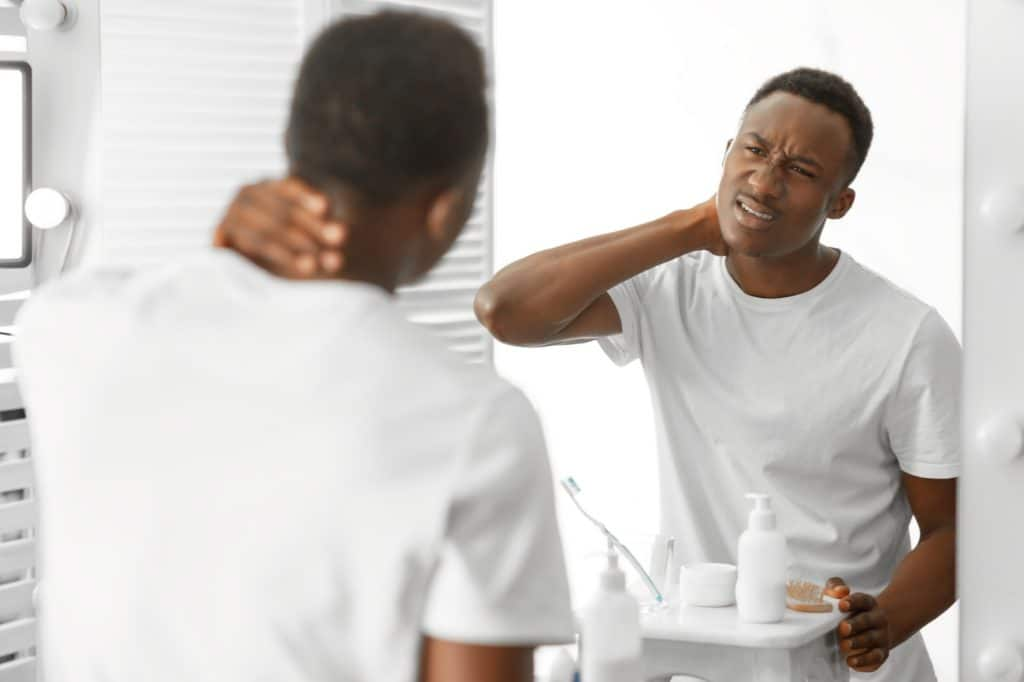 African Man Touching Aching Neck Suffering From Pain In Bathroom