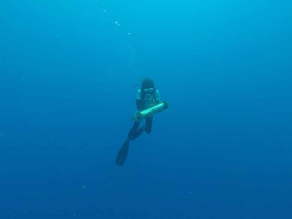 Sous l'eau, Julien de l'association Tité remontant l'hydrophone à la surface. Photo de Thibaud Rossard Ommag.