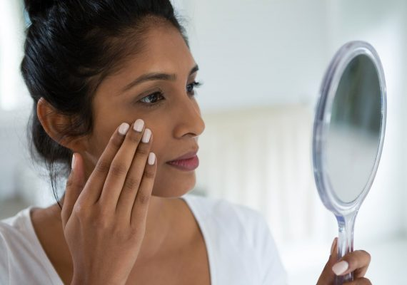 Close-up of woman holding hand mirror